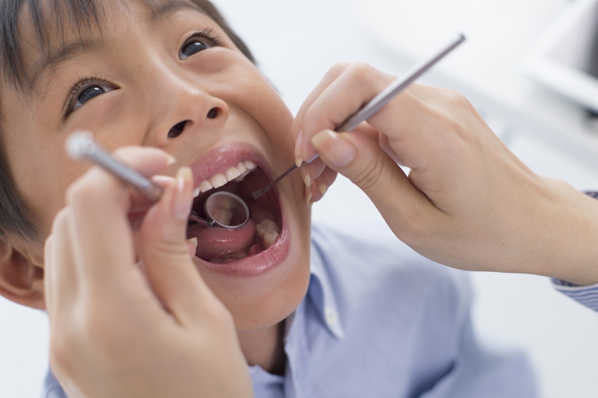 A young boy is examined for dental caries.