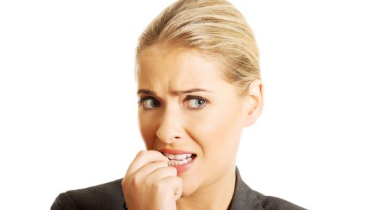 A young blond woman chews her nails out of stress, a habit our Placerville dentists discourage.