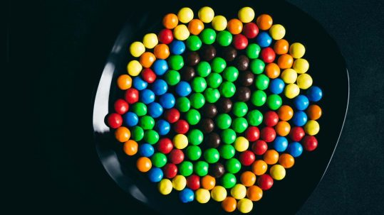 A bowl of candy illustrates the essential question — do they harm the teeth?